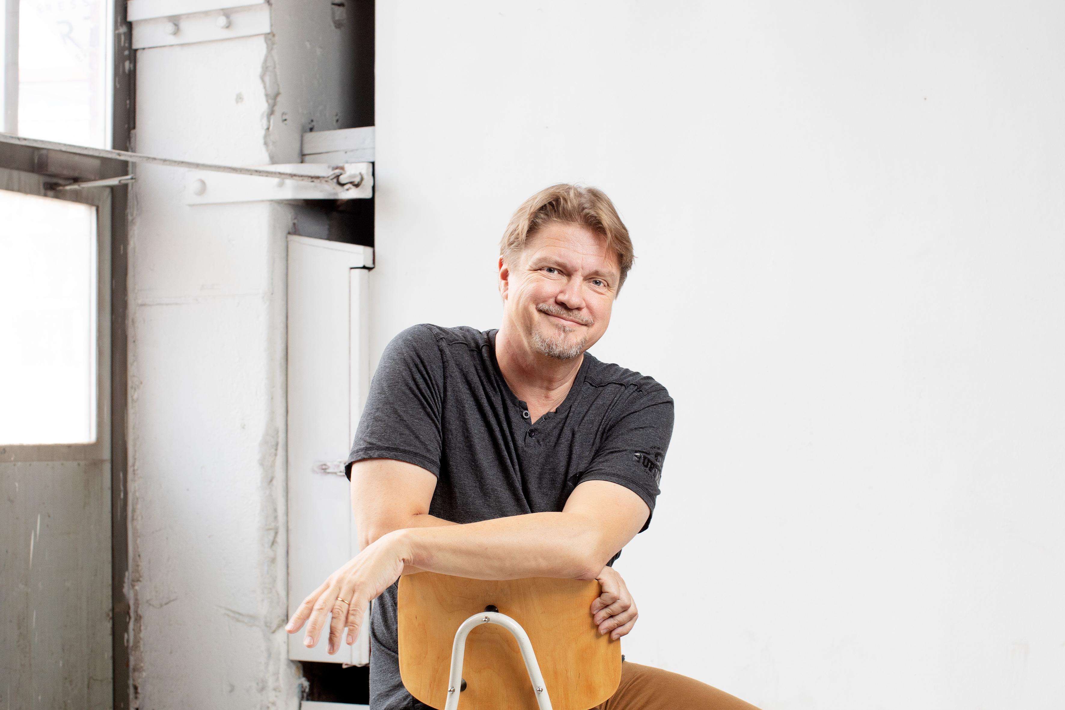 Kuvassa on kirjailija Timo Parvela, joka istuu tuolilla, katsoo kameraa kohti ja hymyilee. Vaalea seinä taustalla.