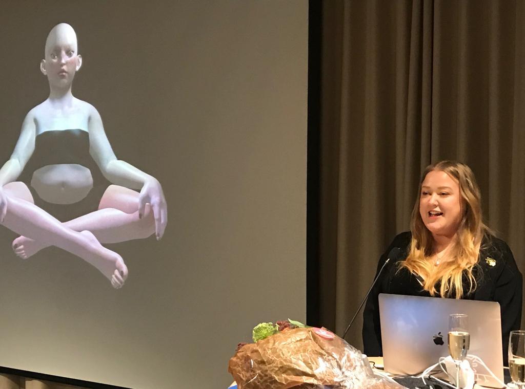 Kuvassa AVEK-palkittu Reija Meriläinen pitää juhlapuhetta. Pöydällä on kuohuviinilasit, kukkakimppu ja laptop. Taustalla näkyy verhot sekä kuva Meriläisen teoksesta, jossa hahmo istuu risti-istunnassa.