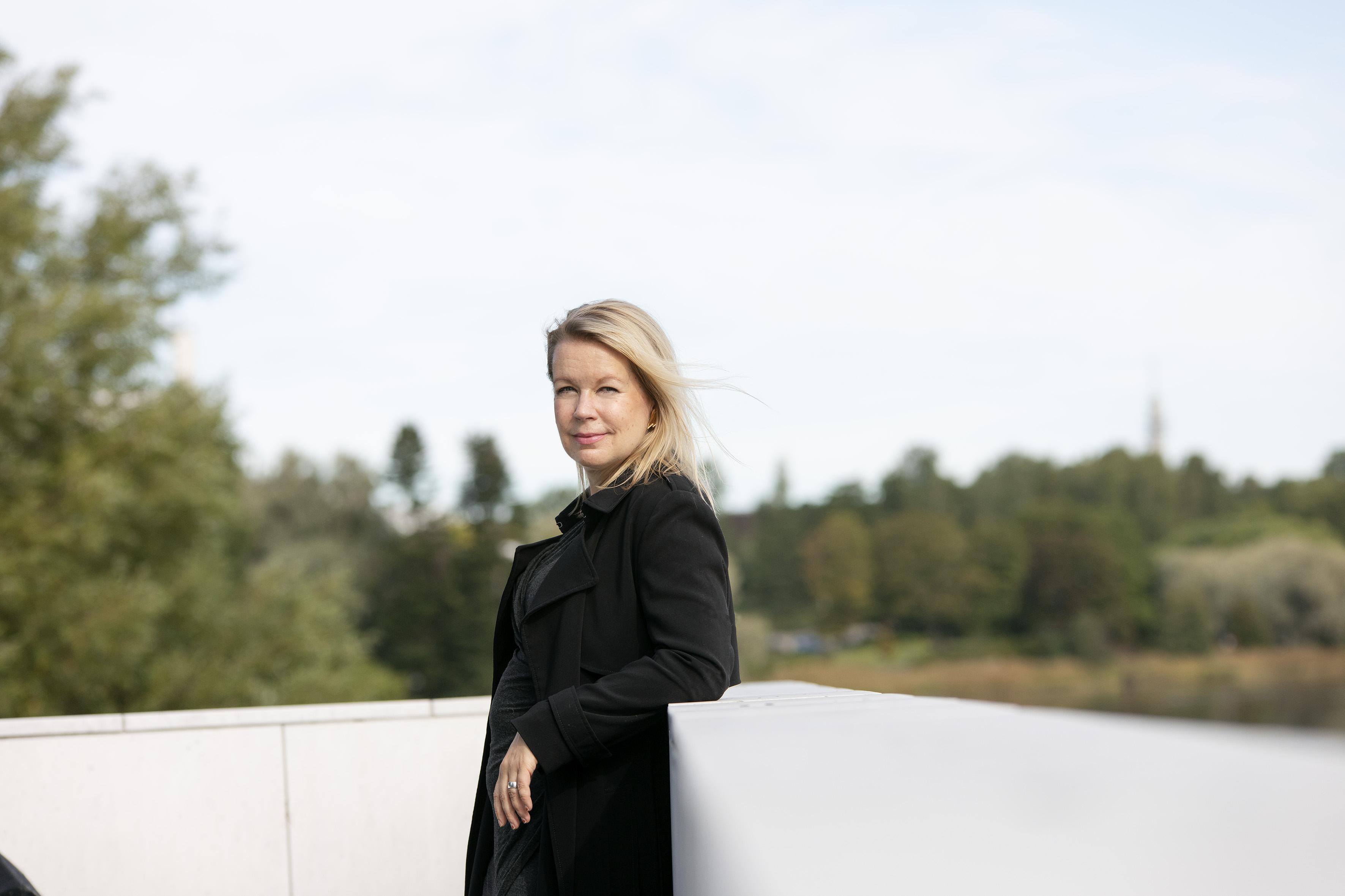 Ulkokuvassa Elina Hirvonen nojaa valkoiseen kaiteeseen, hän katsoo kameraan ja hiukset hulmuaa tuulessa. Taustalla sininen taivas, pilviä ja puita.