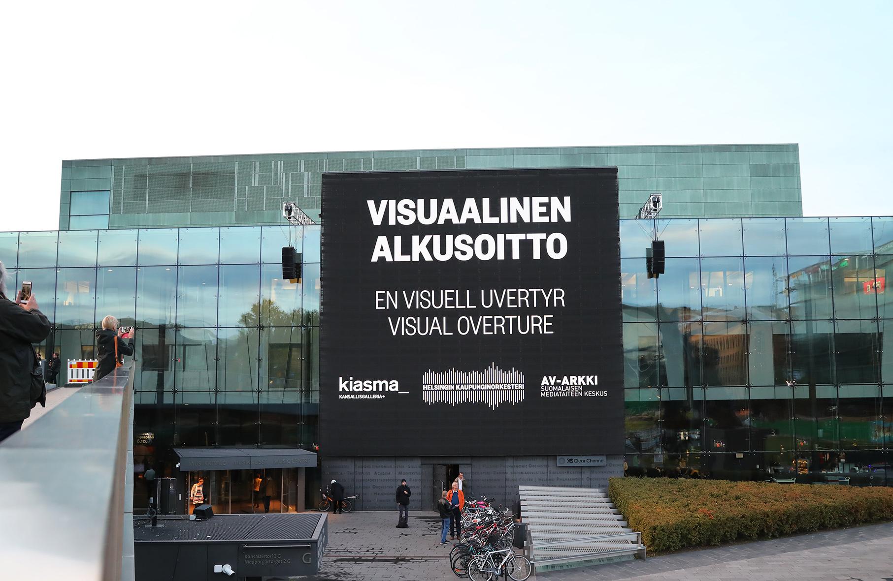 Kuvassa näkyy Helsingin Musiikkitalon seinä ja seinällä oleva ulkonäyttö. Näytöllä näkyy Visuaalinen alkusoitto -mediataideprojektin nimi ja sen järjestäjät Kiasma, Helsingin kaupunginorkesteri ja AV-arkki. Kuvan on ottanut Maarit Kytöharju.