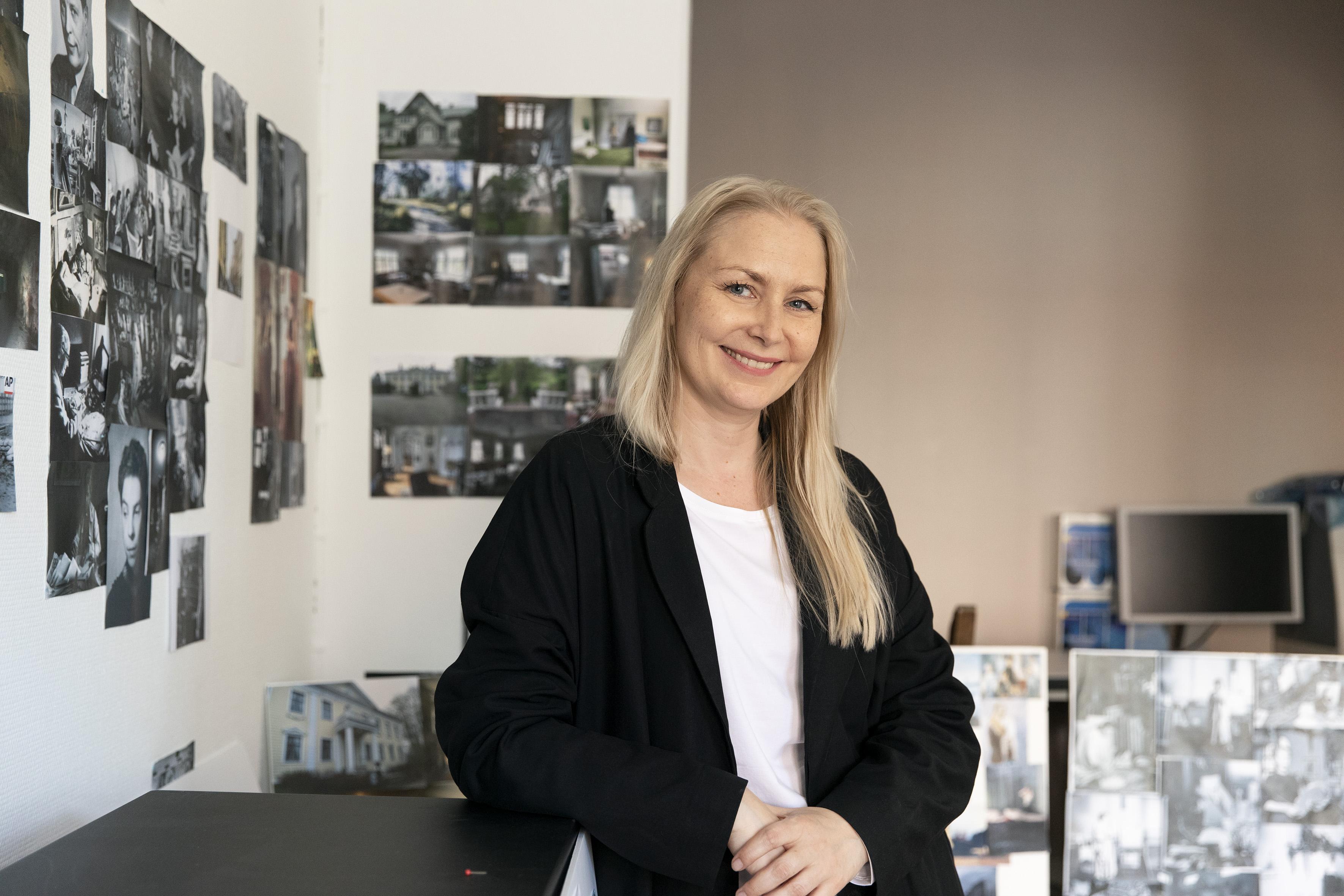 Kuvassa Zaida Bergroth nojaa tasoon ja katsoo suoraan kameraan hymyillen. Taustalla näkyy seinään kiinnitettyjä erilaisia valokuvia.