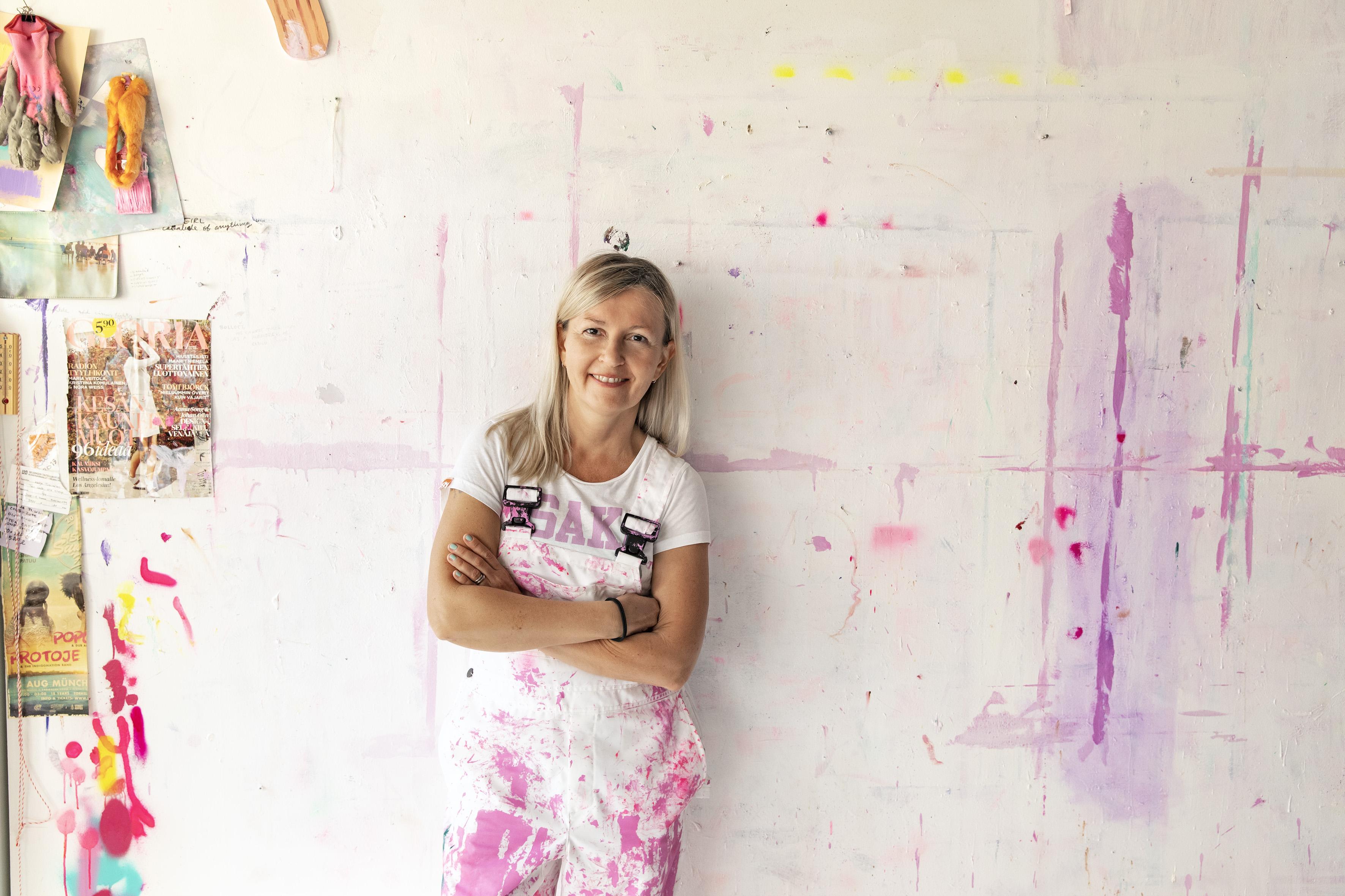 Katja Tukiainen nojaa valkoiseen seinään, jossa on vaaleanpunaisia ja liiloja maalitahroja. Hän katsoo suoraan kameraan ja hymyilee. Hänellä on yllään valkoiset haalarit, jotka ovat myös vaaleanpunaisen maalin peitossa.