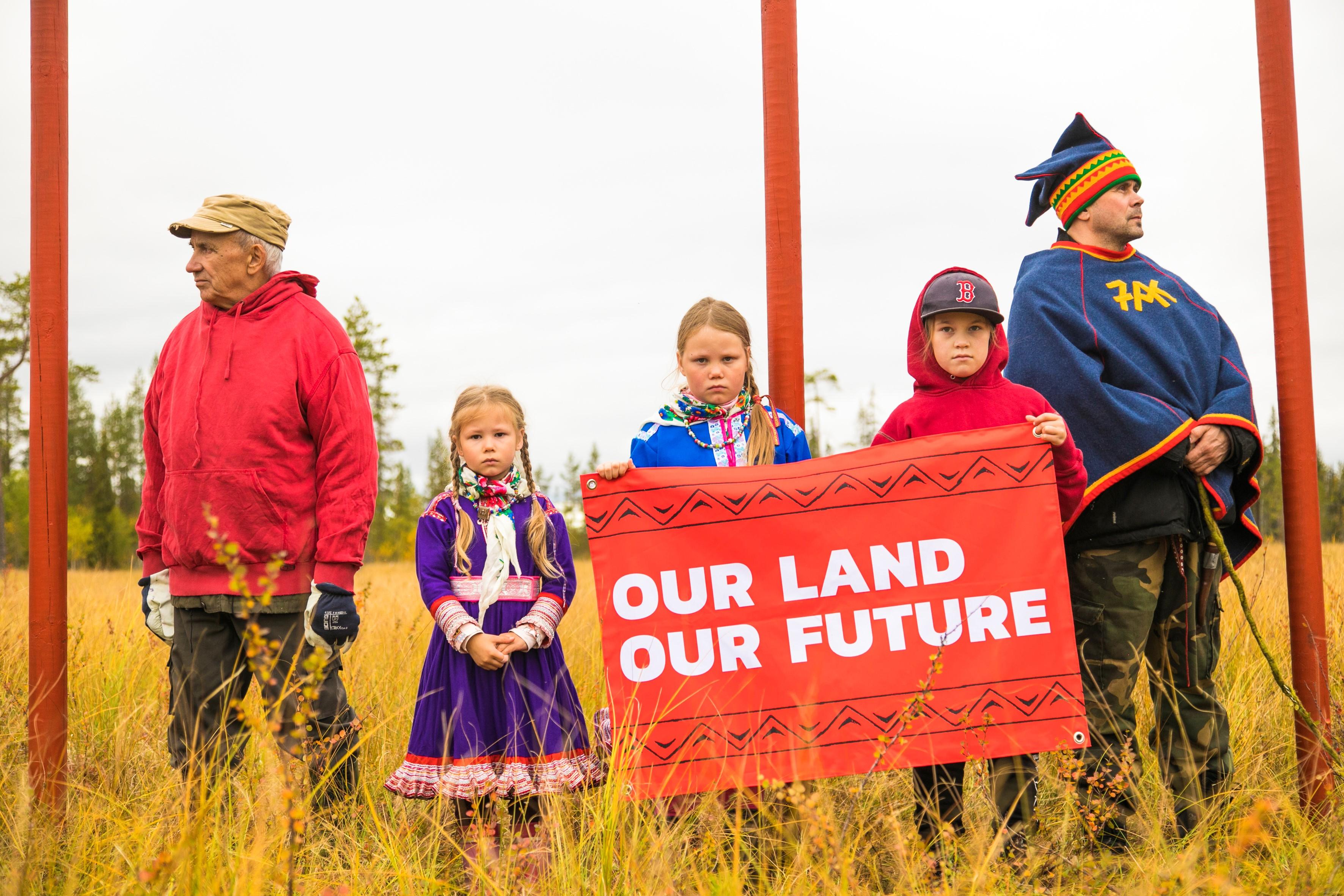 """Kuvassa reunoilla kaksi aikuista ja keskellä kolme lasta peltomaisemassa. Lapset katsovat suoraan kameraan ja pitelevät kylttiä, jossa lukee """"Our land, our future""""."""