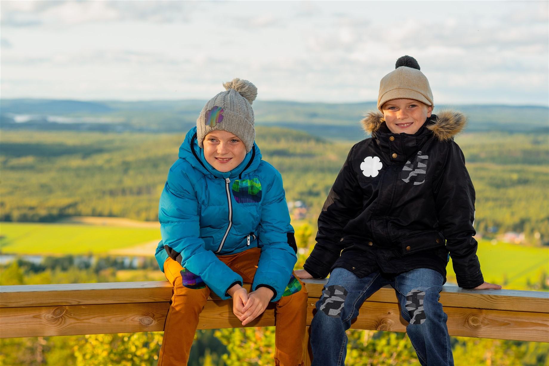 Kuvassa kaksi poikaa istuu kaiteella syksyisessä peltomaisemassa. Heillä on yllään syys- tai talvivaatteet ja vaatteissa on Oikiat Designin kehittämiä heijastavia Vaatelaastareita.