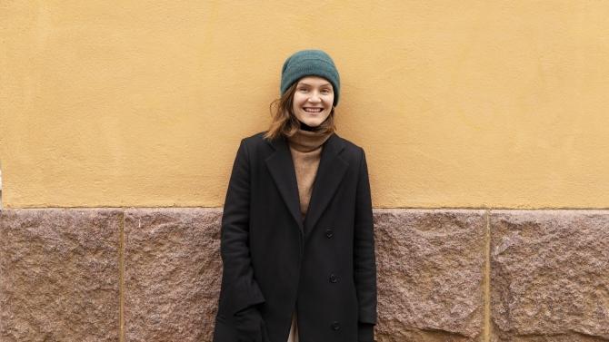 Kuvassa Ronja Salmi nojaa oranssiin seinään ja katsoo kameraan hymyillen. Hänellä on vihreä pipo ja musta takki.