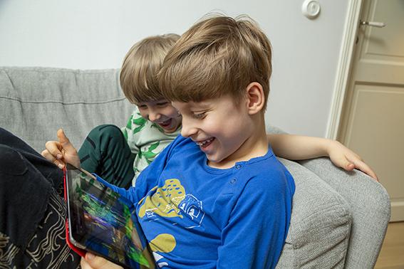 Kaksi poikaa sohvalla katsomassa pädiä