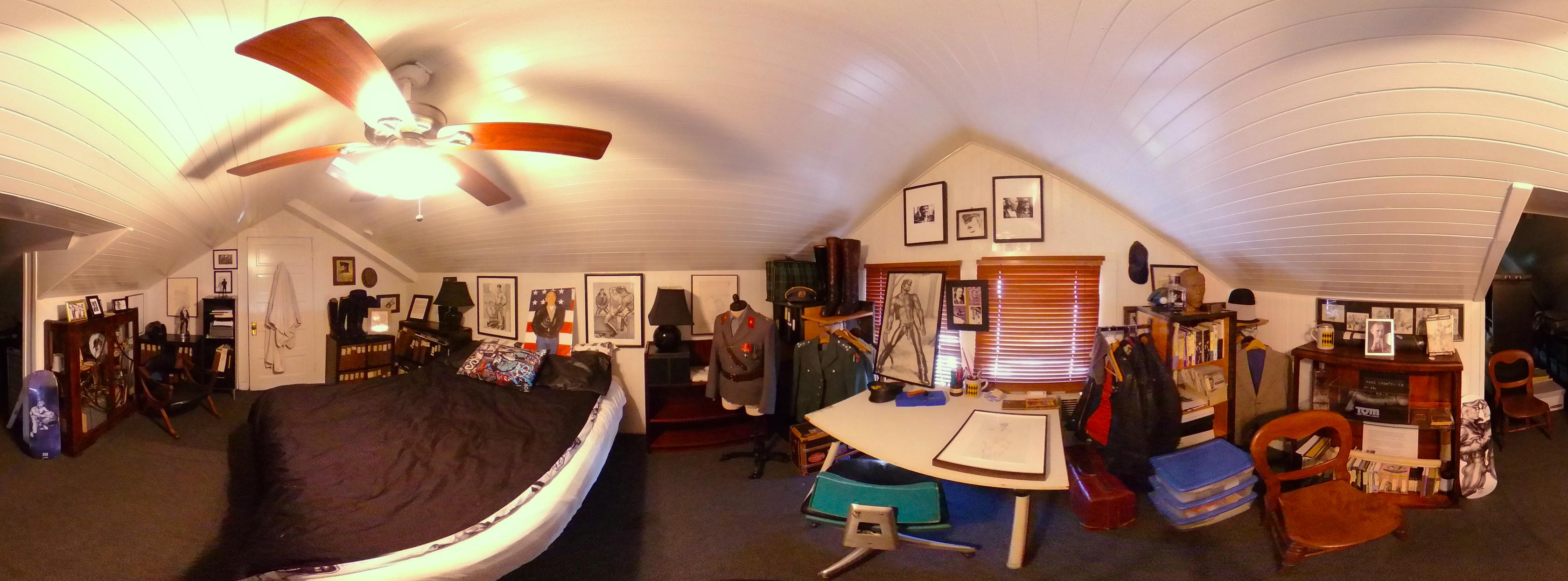 Panoraama Tom of Finlandin huoneesta The Tom Housessa. Kuvassa näkyy paljon erilaista tavaraa, kuten tauluja, sänky, pöytä, ikkuna, sälekaihtimet ja kattotuuletin.
