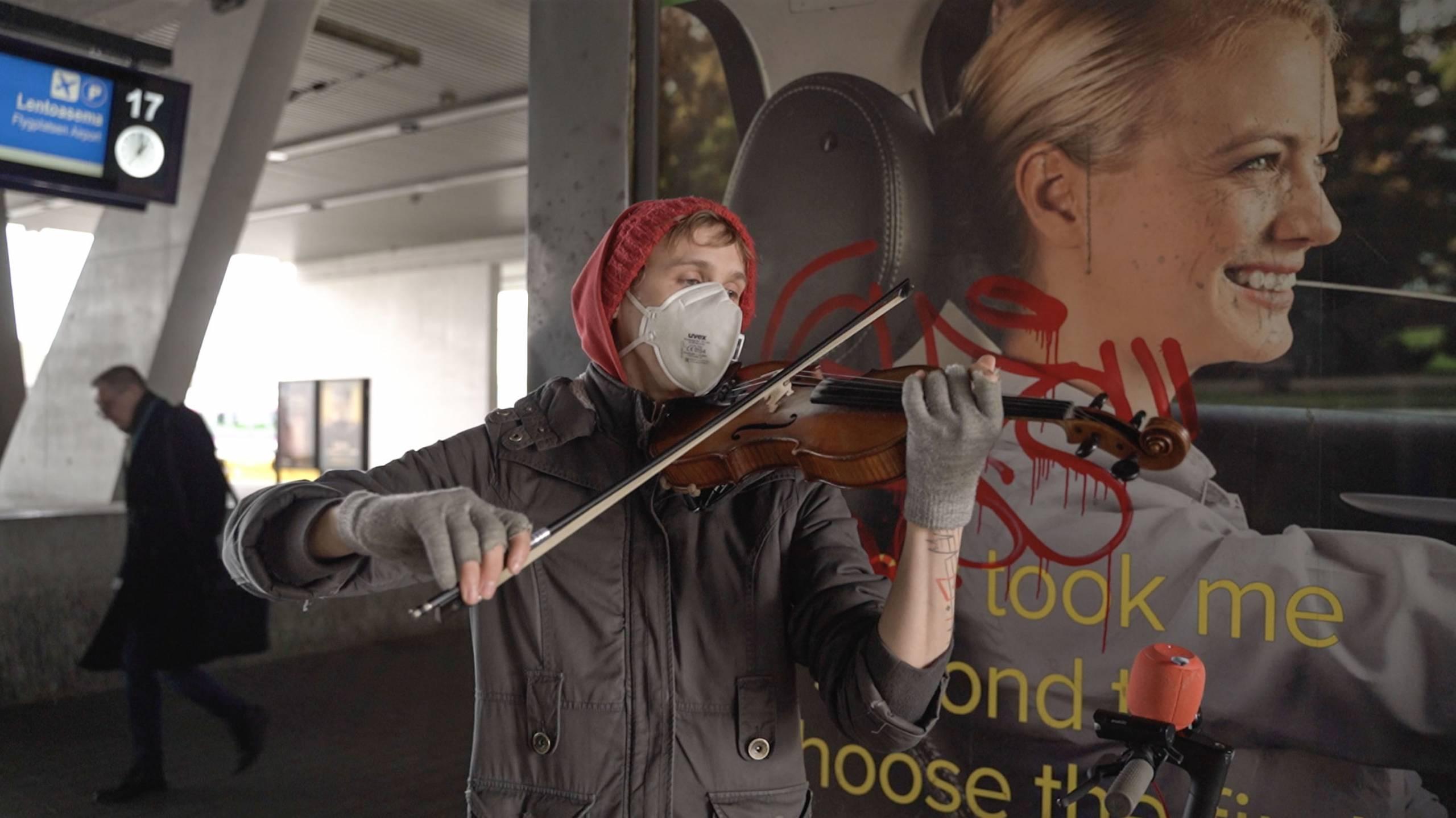 Otos Poikkeustila-projektista. Mies soittaa viulua harmaassa asussa, valkoinen kasvimaski kasvoilla. Seisoo mainoskuvan edessä, taustalla näkyy juna-asema.