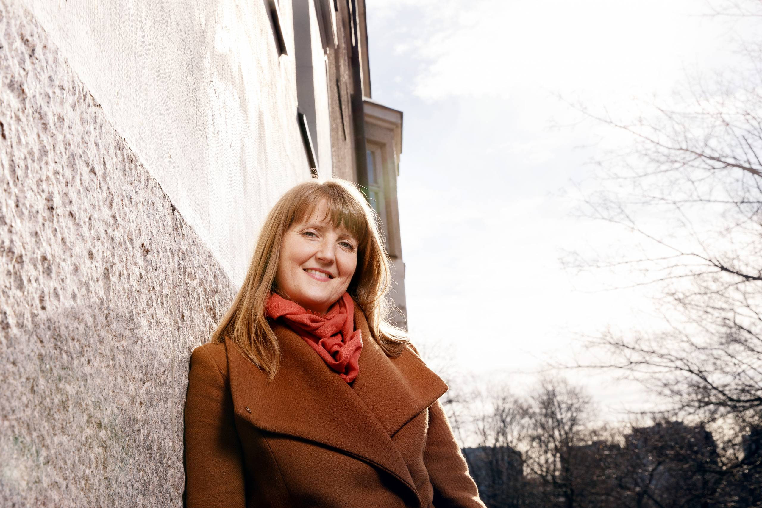 Emmi Jouslehto leaning on a wall and look straight in the camera. A building and trees in the background.