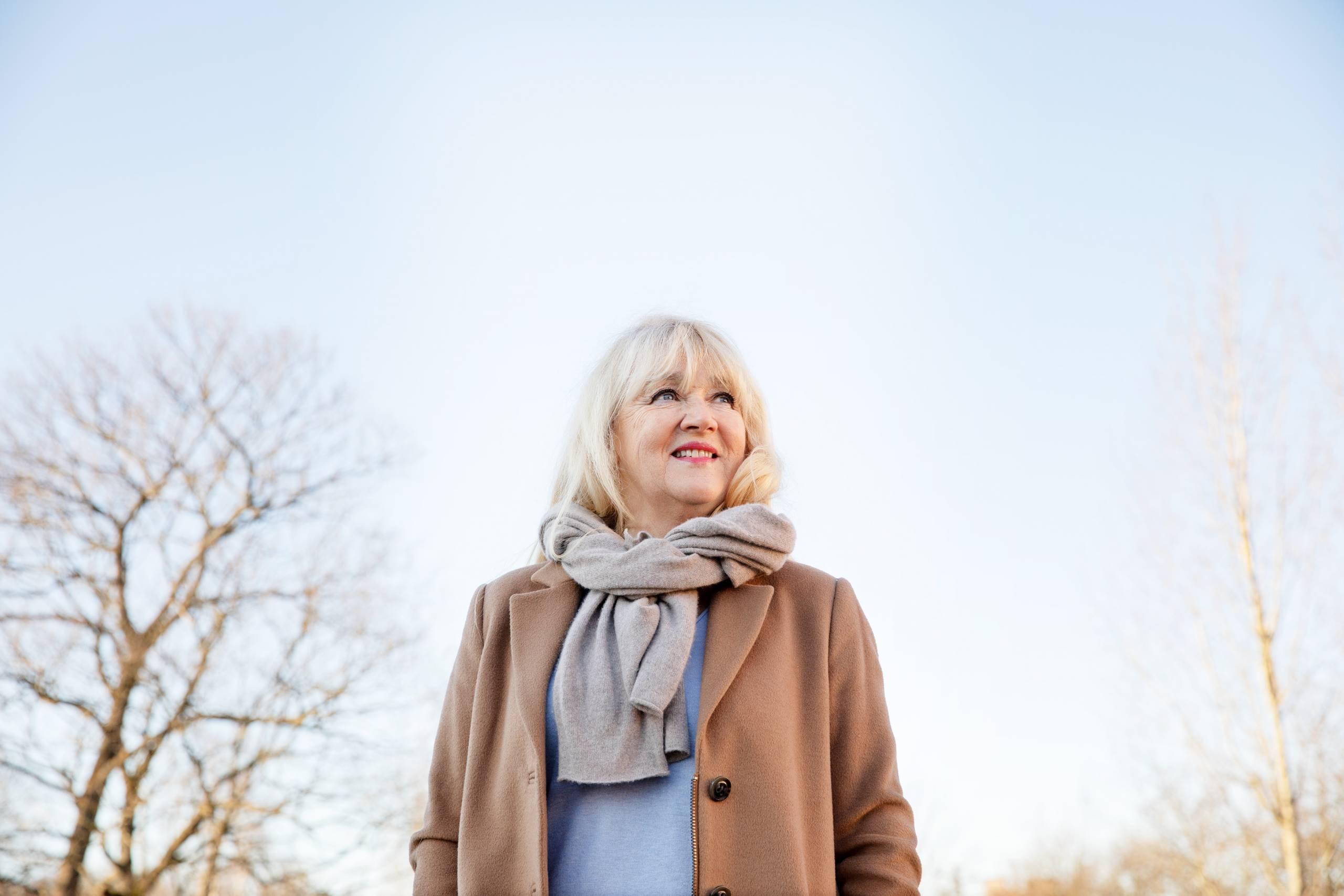 Näyttelijä Jaana Saarinen seisoo ulkona. Taustalla näkyy puita.