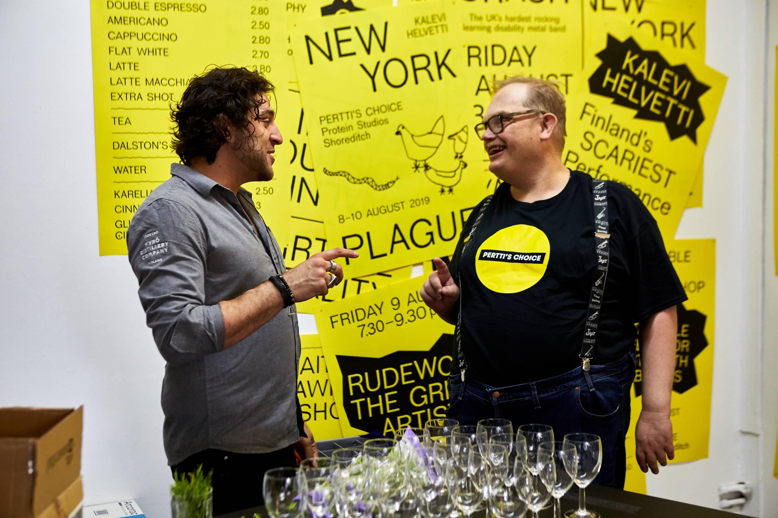 Pertti's Choice pop up -tapahtumasta Lontoosta 2019. Kaksi miestä juttelee hymyillen. Edustalla näkyy tyhjiä viinilaseja, Taustalla keltaisia julisteita.