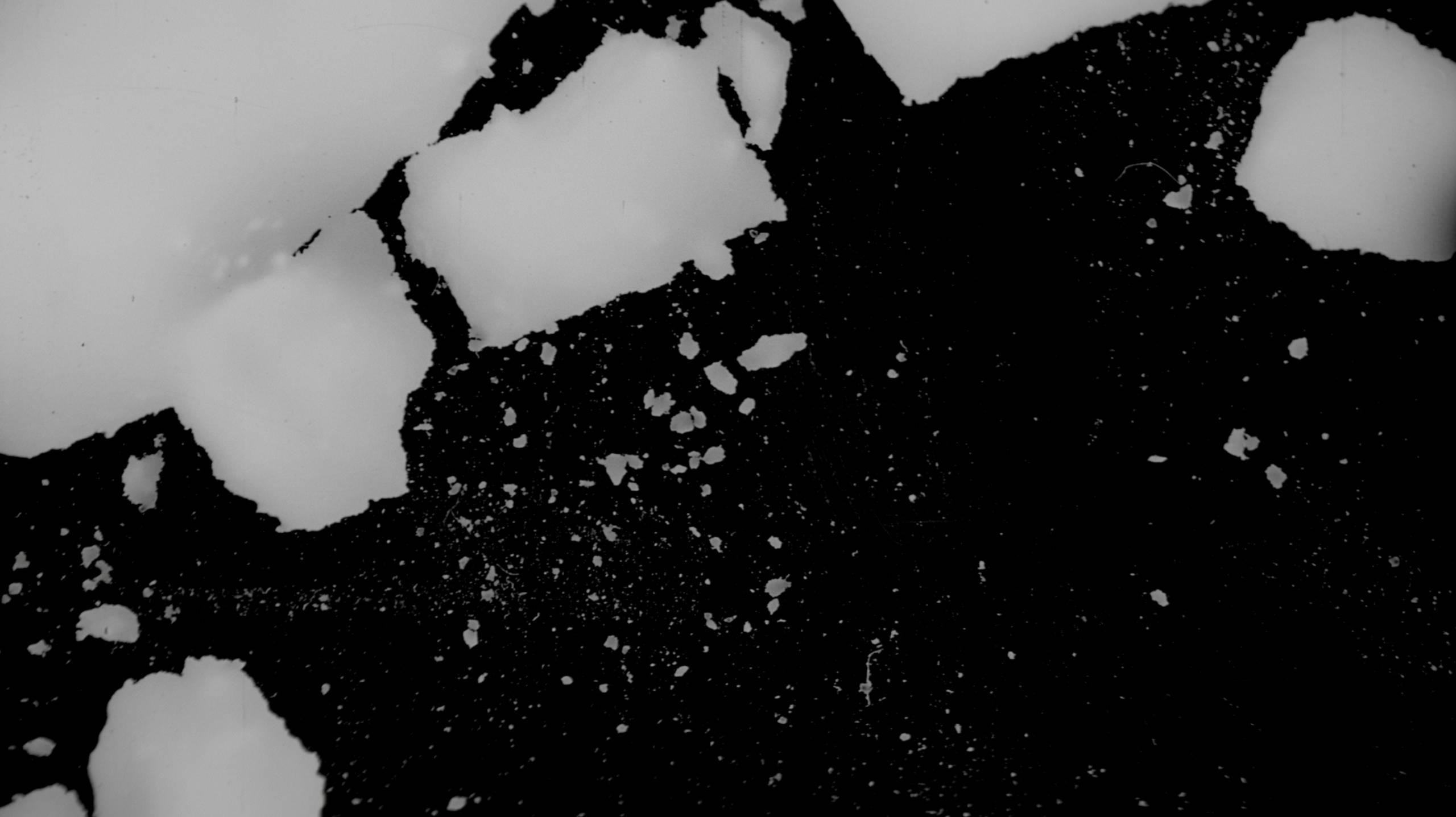 Stillkuva Mannerlaatta-elokuvasta. Mustalla pinnalla näkyy valkoisia lohkareita ja murusia.