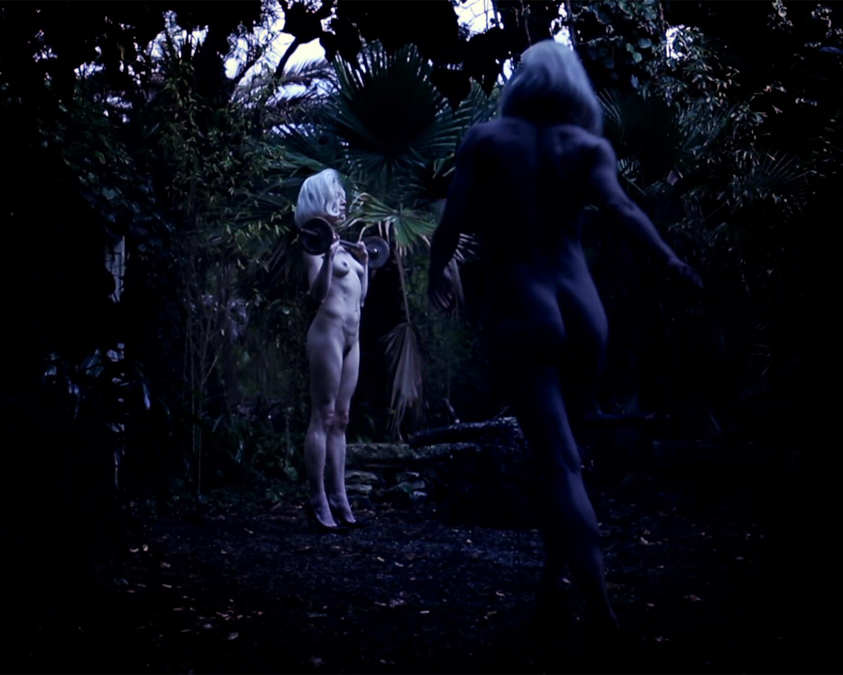 Kuvakaappaus teoksesta Untitled Ritual 3. Nainen seisoo metsässä levypainotanko käsissään. Hän on alasti lukuun ottamatta korkokengiä, ja hänellä on vaaleat hiukset. Etualalla näkyy toinen, myös vaaleahiuksinen ja alaston nainen. Hän on selkä kameraa kohti ja vaikuttaa olevan liikkeessä.