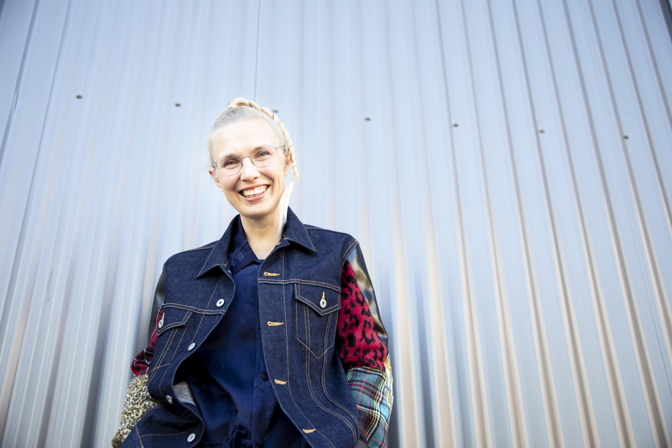 AVEK-palkinnonsaaja 2020 Jenna Sutela, joka hymyilee ja katsoo suoraan kameraan. Taustalla metallinen seinä.
