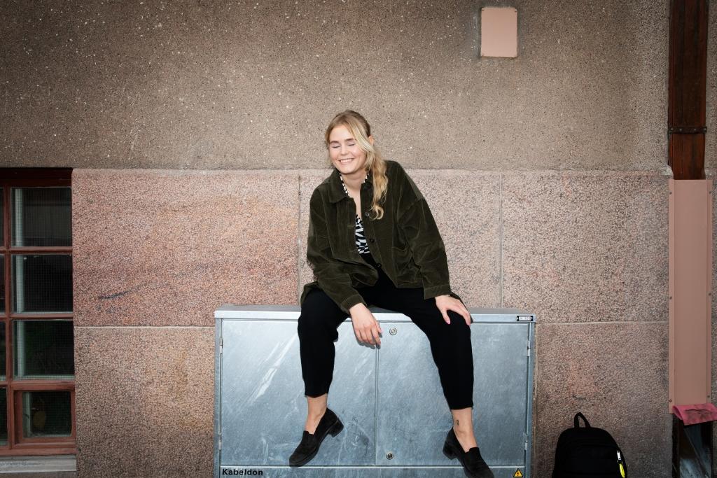 Taiteilija Aliina Kauranne istuu hymyillen sähkökaapin päällä, taustalla rakennuksen seinää