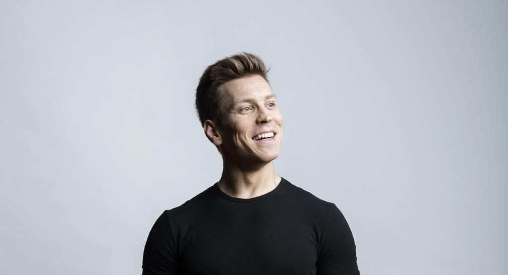 Antti Holma katsoo sivulle ja hymyilee. Seisoo vaaleaa taustaa vasten.