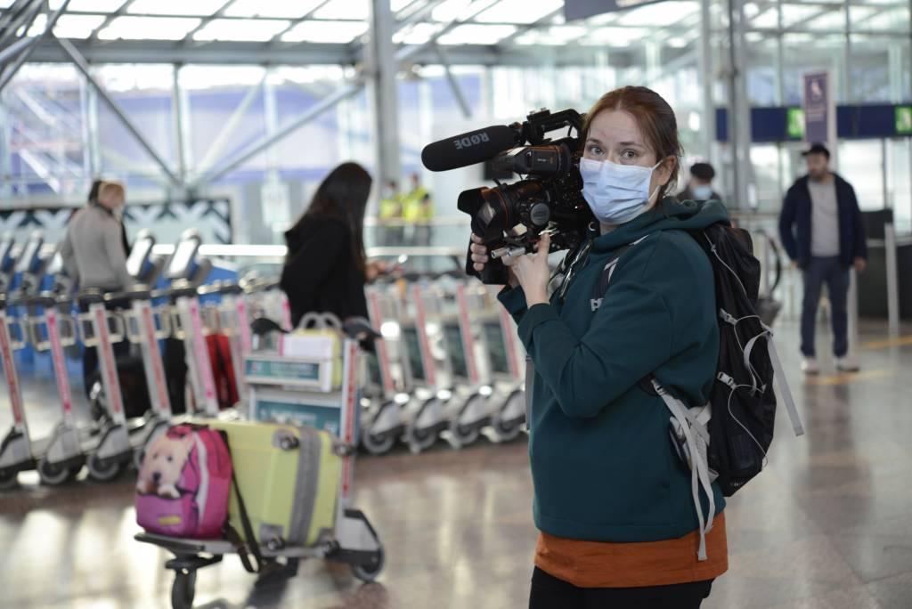 Yksi Poikkeustila-elokuvan tekijöistä, Saija Mäki-Nevala, elokuvakamera kädessä ja maski päällä lentokentällä. Taustalla näkyy lentokentän aulaa ja ihminen matkalaukkujen kanssa.