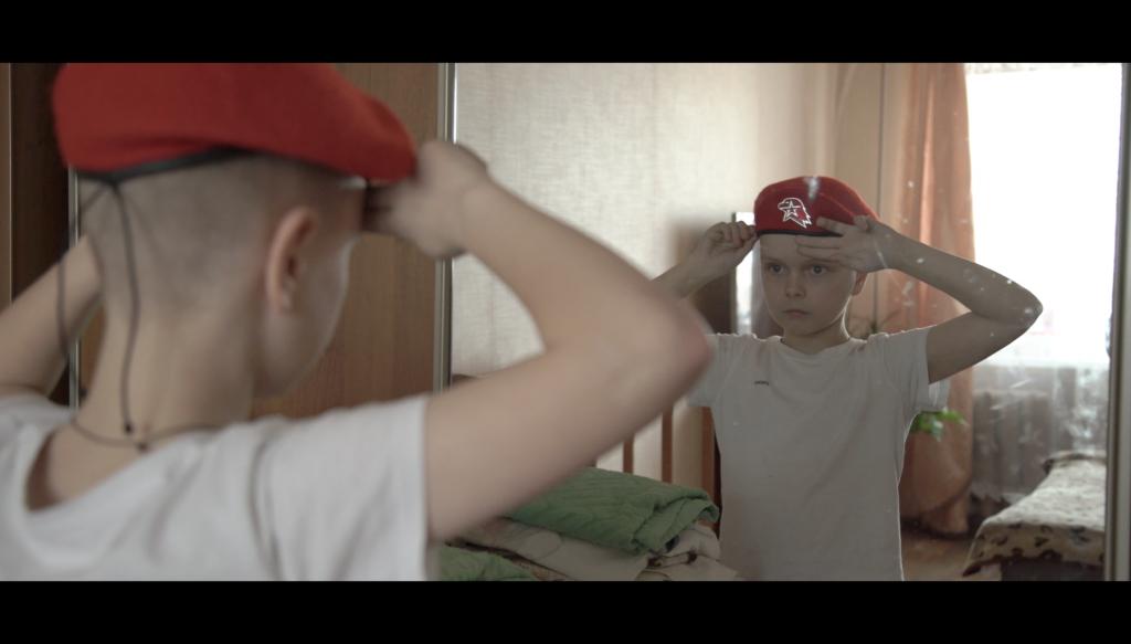 Poika katsoo peiliin ja tekee sotilaallisen tervehdyksen.