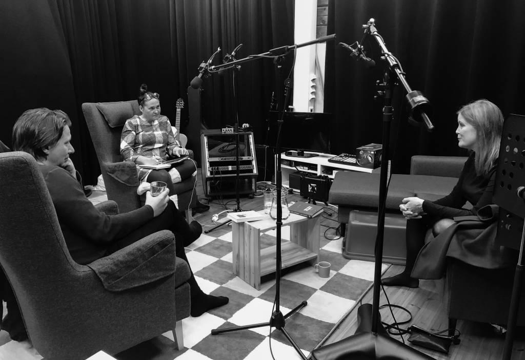 Mustavalkoinen kuva äänitystudiosta: Jan Forrström, Ulla Simonen ja Reetta Aalto istuvat nojatuoleissa, ympärillä mikkejä.