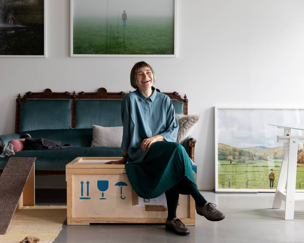 Elina Brotherus kuvattuna työhuoneellaan Kaapelitehtaalla. Hän istuu sohvapöydän päällä, nauraa ja katsoo kameraan. Taustalla sohva, matto ja valokuvatauluja.
