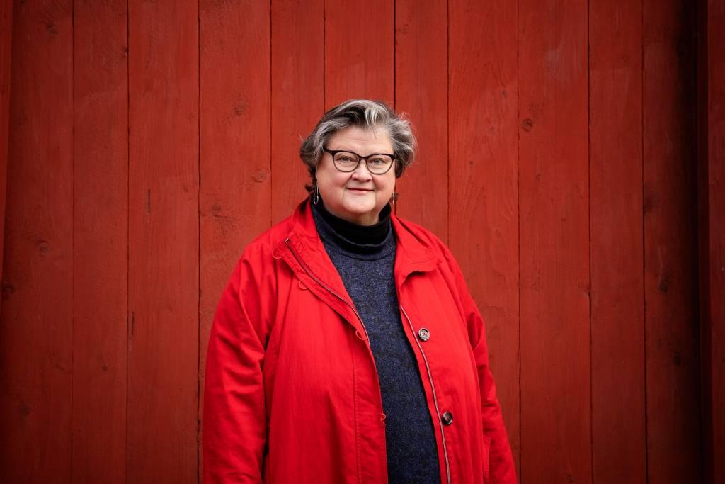 Marikki Hakola seisoo, hymyilee ja katsoo suoraan kameraan.. Taustalla punainen seinä.