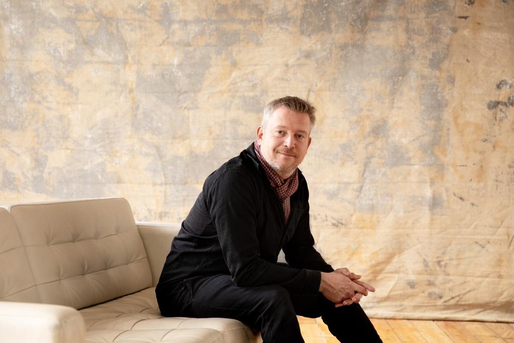 Käsikirjoittaja ja ohjaaja Atte Järvinen istuu ja hymyilee kameralle