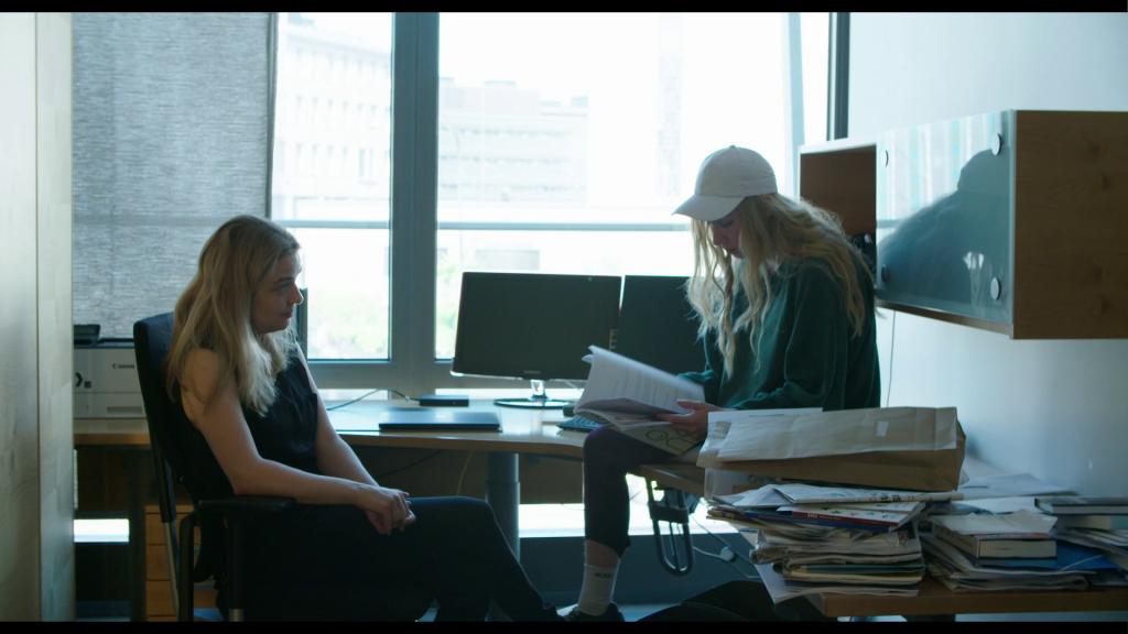 Mai ja Saila istuvat jonkinlaisessa toimistotilassa, Mai katsoo Sailaa ja Saila kädessään pitämiä papereita. Mai istuu tuolilla, Saila pöydän päällä. Taustalla ikkuna, tietokoneruutuja ja etualalla kasapapereita.