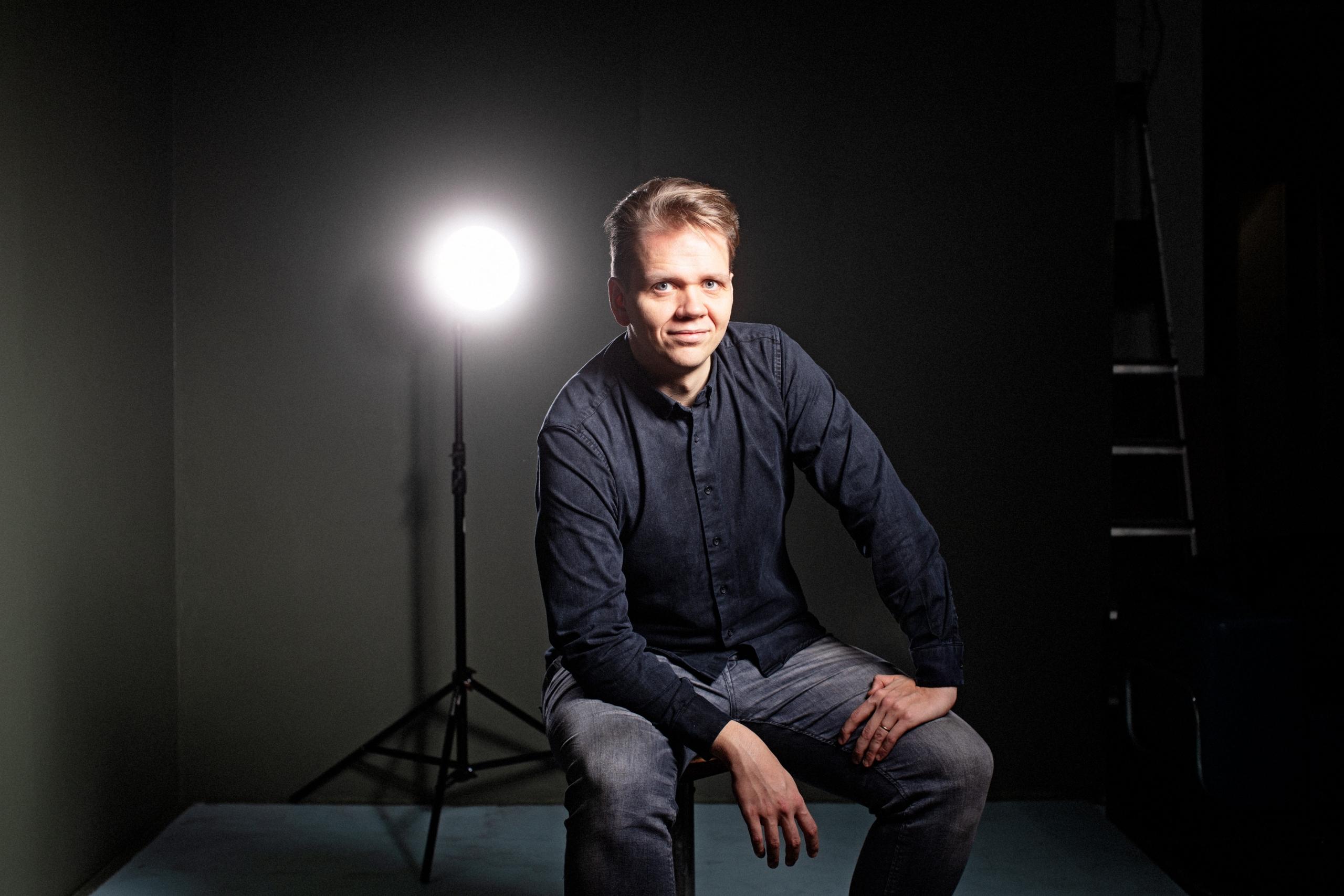 Leikkaaja Jussi Rautaniemi istuu ja hymyilee kameralle valokuvastudiossa.