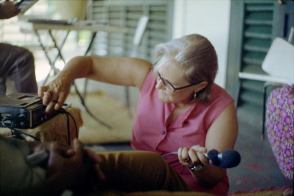 Monica Flaherty istuu lattialla, säätää äänityslaitetta.