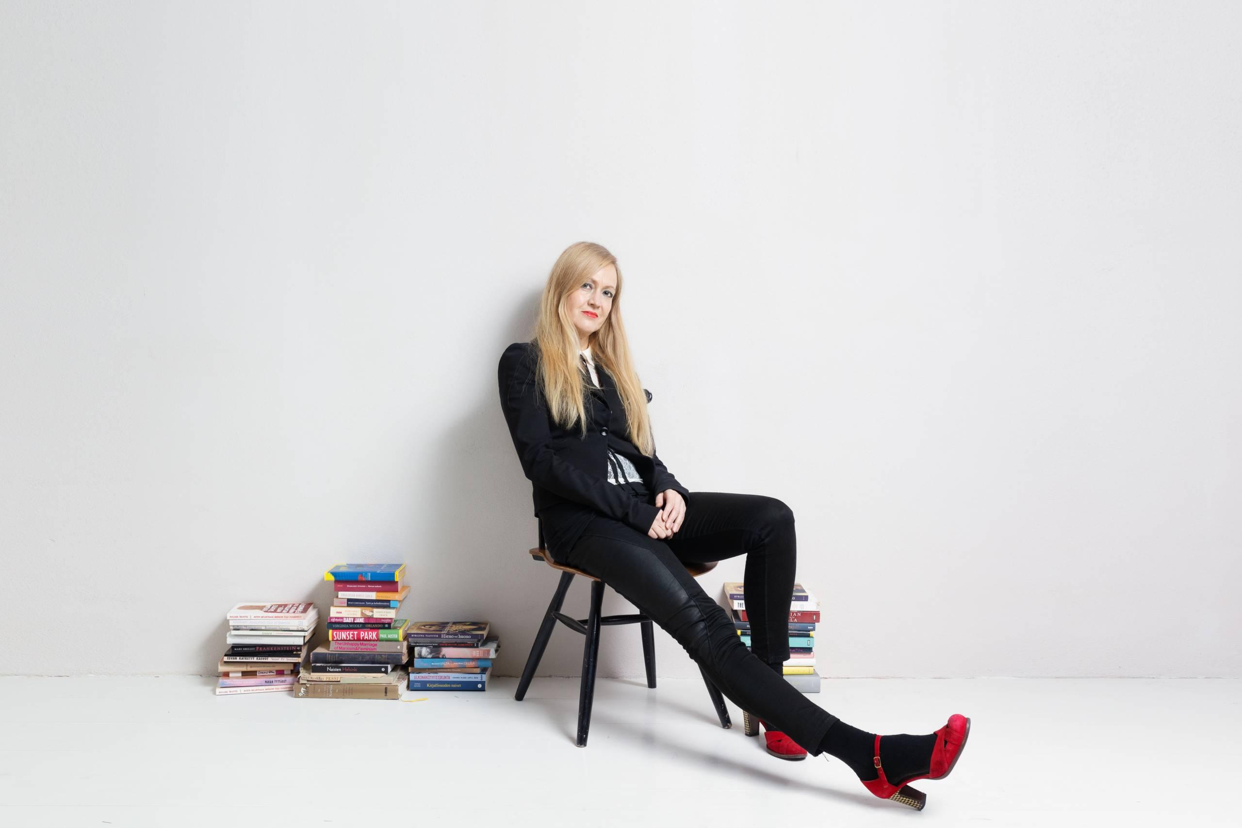 Kirjailija Eveliina Talvitie istuu tuolilla mustassa asussa, jalassa kirkkaanpunaiset korkokengät. Jalat ovat kuvassa etualalla. Talvitien vieressä, molemminpuolin on lattialla kirjakasoja.