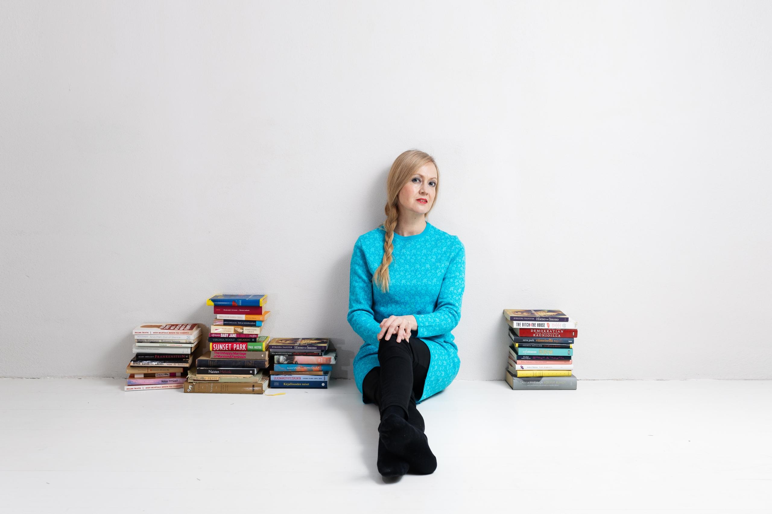 Kirjailija Eveliina Talvitie istuu lattialla nojaten seinään. Hänen vierellään molemminpuolin lattialla on kirjakasoja.