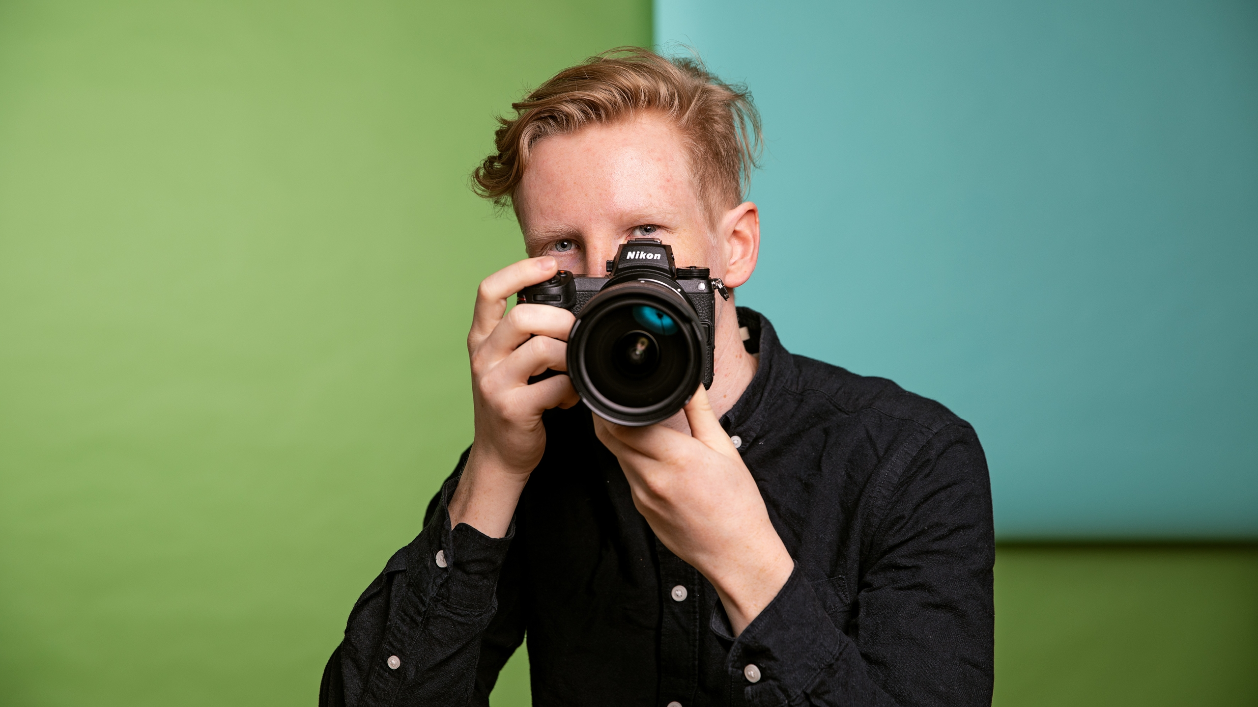 Luontokuvaaja Konsta Punkka poseeraa kameran kanssa