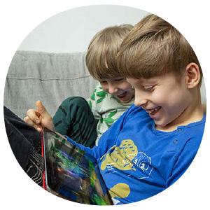 Kaksi lasta katsoo tablettia nauraen.