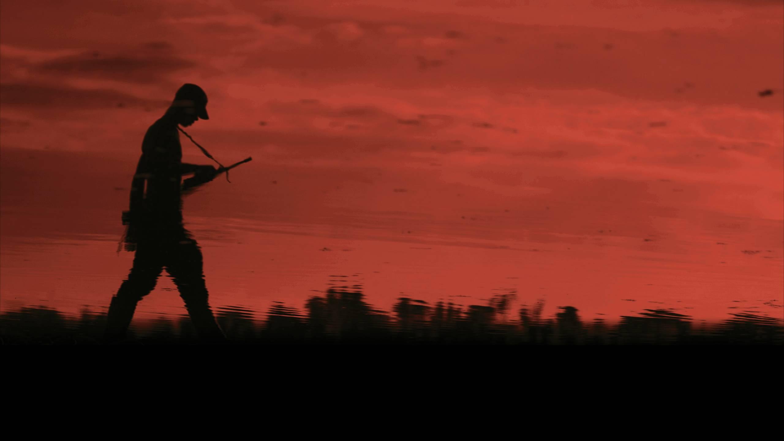 Mies kävelee aseen kanssa. Otos elokuvasta Colombia in my Arms.