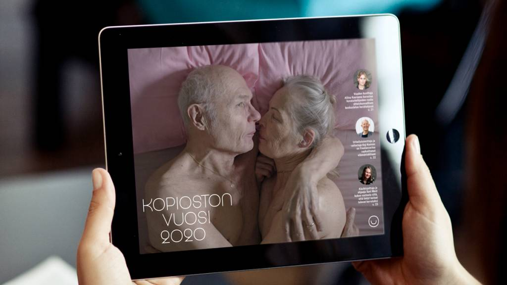 The cover of Kopiosto's year 2020 brochure can be seen on an iPad that someone is holding.