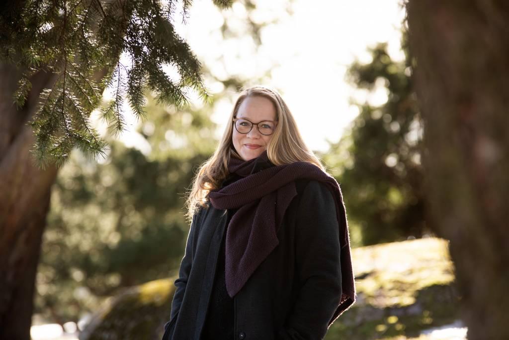 Toimittaja ja kirjailija Anu Silfverberg hymyilee ja katsoo kameraan. Taustalla metsää.