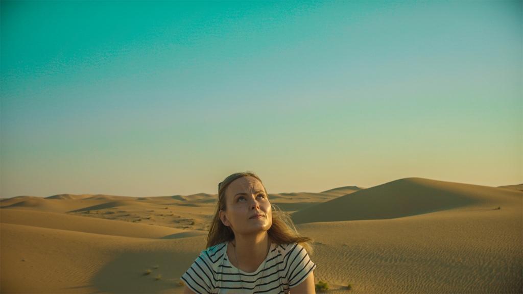Keskellä kuvaa on nainen, joka katsoo ylöspäin. Taustalla aavikko ja taivas.