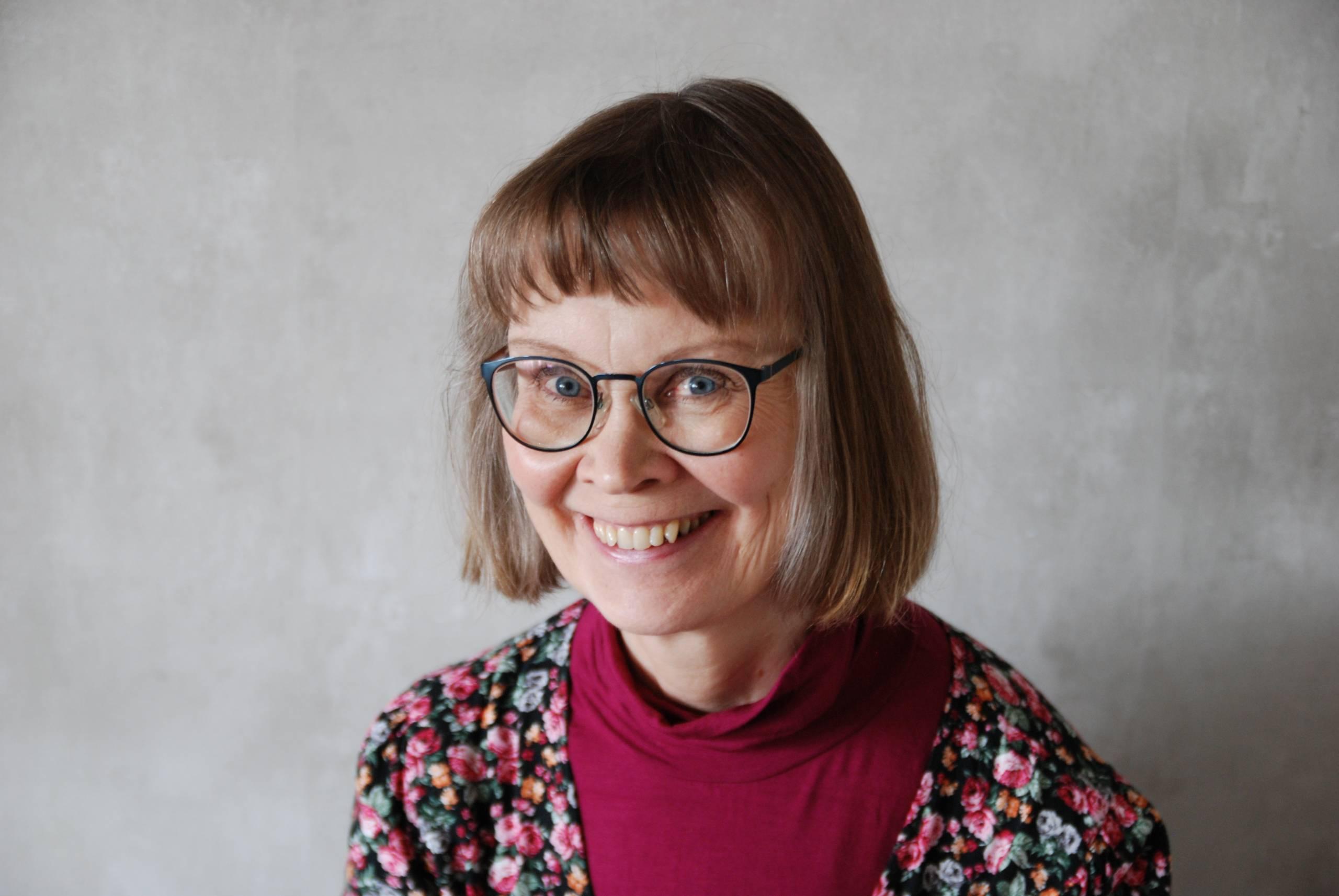 Kääntäjä Arja Pikkupeura hymyilee kameralle harmaata taustaa vasten