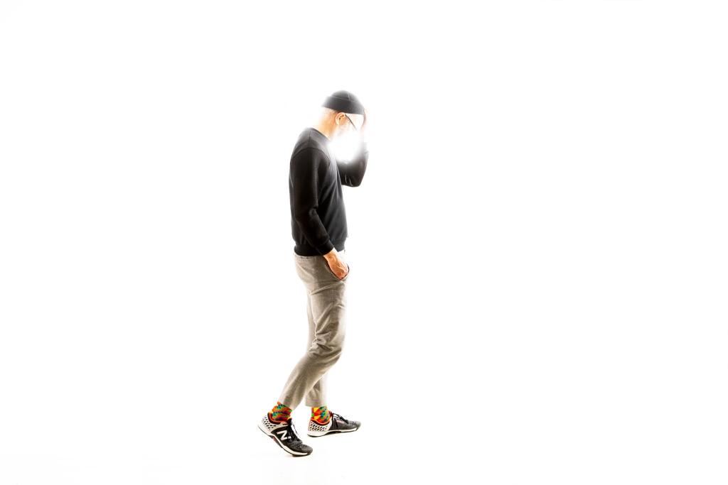 Timo Wright seisoo sivuttain, keskellä kuvaa ja käsi pitelee päätä. Tausta on täysin valkoinen.