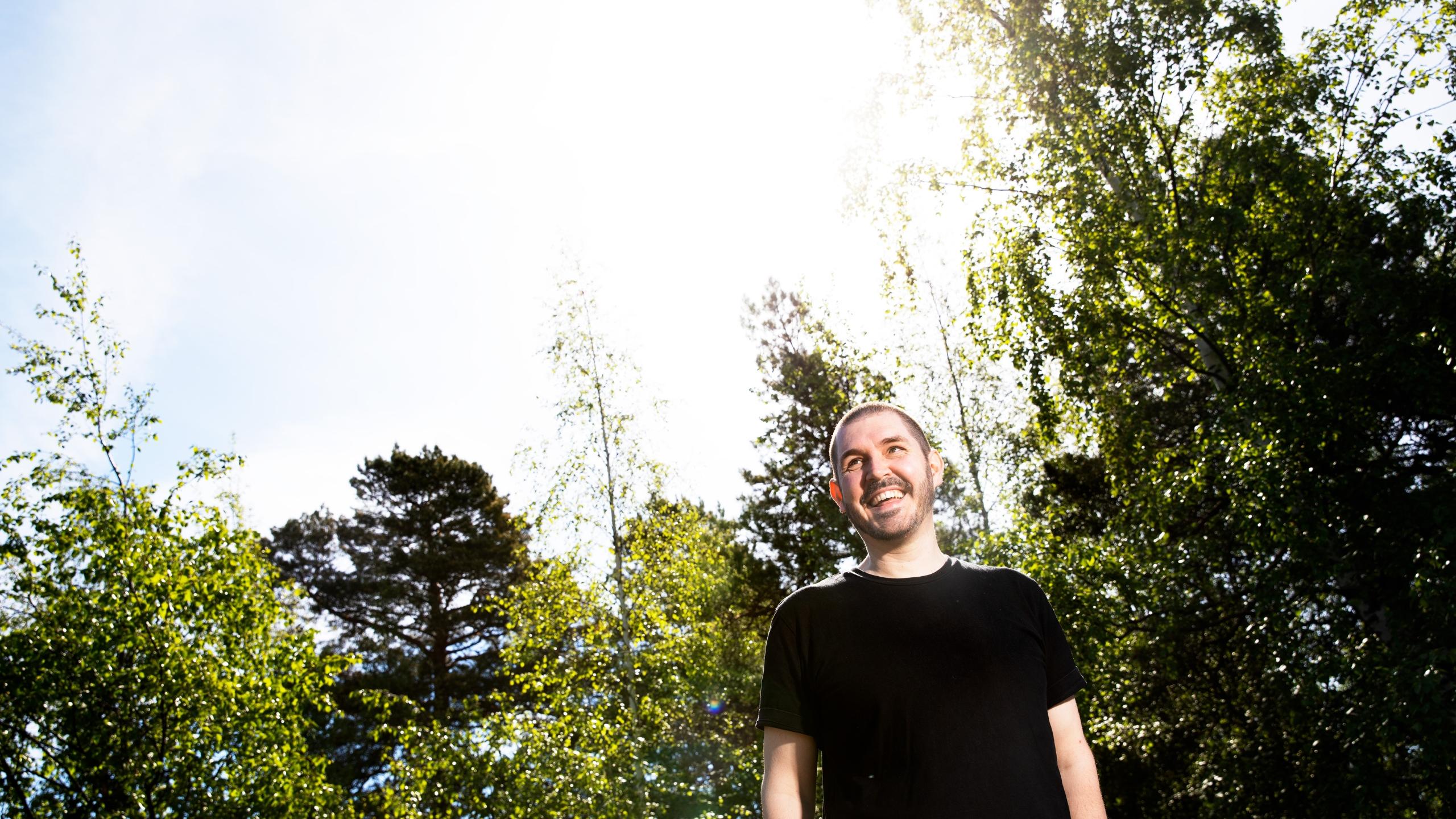Lavastaja Kari Kankaanpää hymyilee. Taustalla puumaisema.