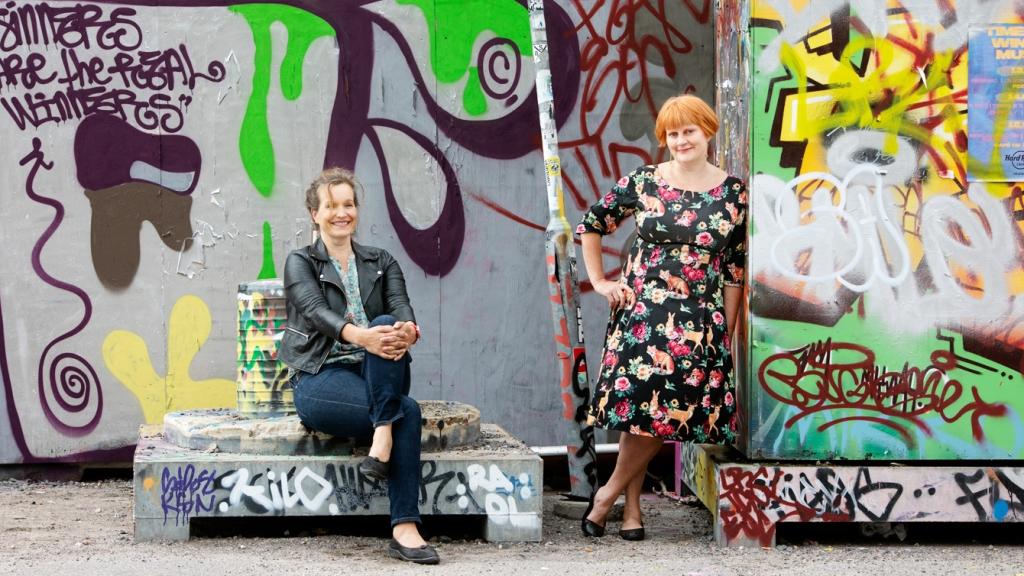 Laaja kokokuva. Vuoksenmaa istuu vasemmalla, Hyytiä nojaa seinään. Molemmat hymyilevät ja katsovat kameraa. Miljöönä on värikäs graffitiseinä ulkona.