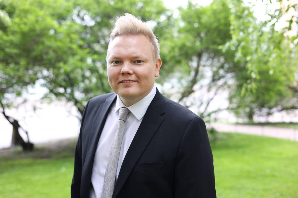 Ministeri Antti Kurvinen kuvattuna puistomaisemassa